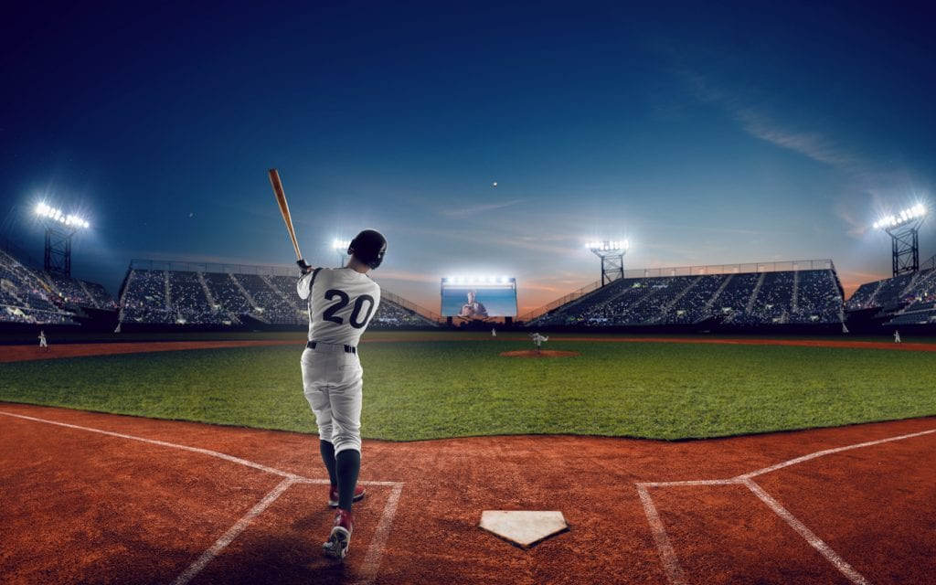 Baseball player at professional baseball stadium in evening during a game.